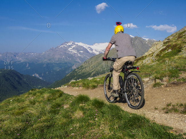 Italy Lombardy- Passo di Val Viola- Man riding e-bike in the mountains with action cam on his helmet
