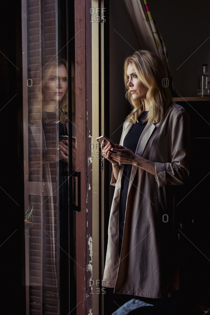 Portrait of fashionable young woman looking out of window