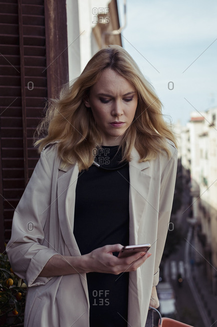 Portrait of blond young woman looking at cell phone