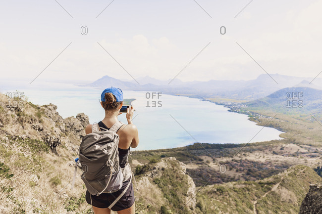 Mauritius- Riviere Noire District- Woman photographing with smartphone the coast- view from Mount Le Morne Brabant