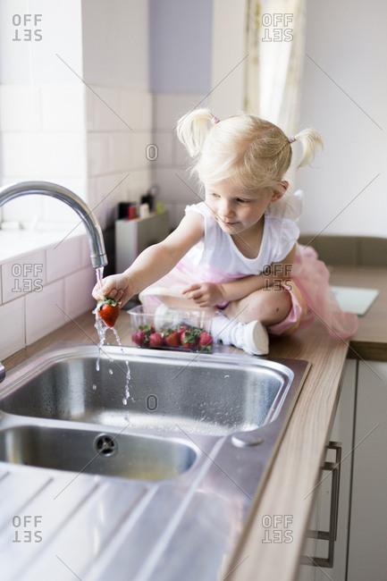 Little girl sitting on worktop in the kitchen washing strawberries