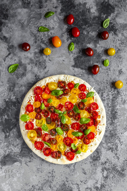 Unbaked pizza with tomatoes and basil leaves