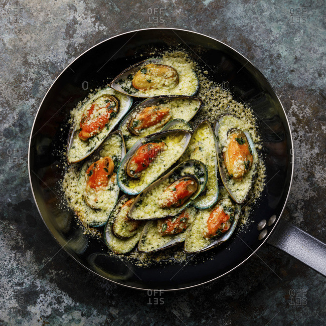 Mussels Clams Kiwi with parmesan cheese in cooking pan on metal background
