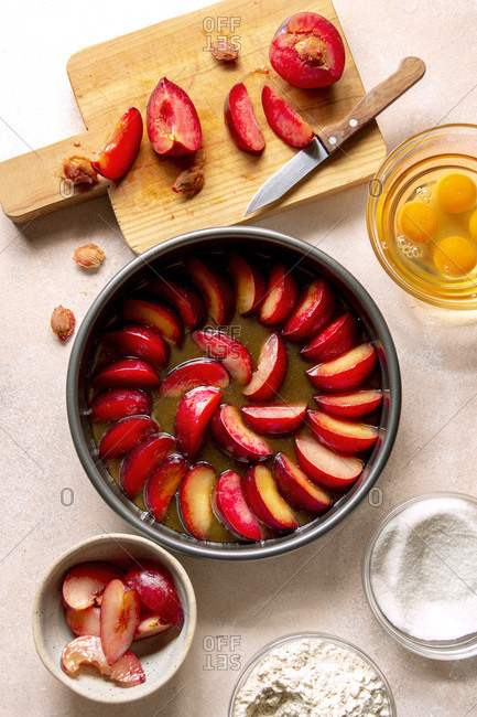 Preparing an upside-down plum cake, plums, eggs, flour and sugar in bowls on the table