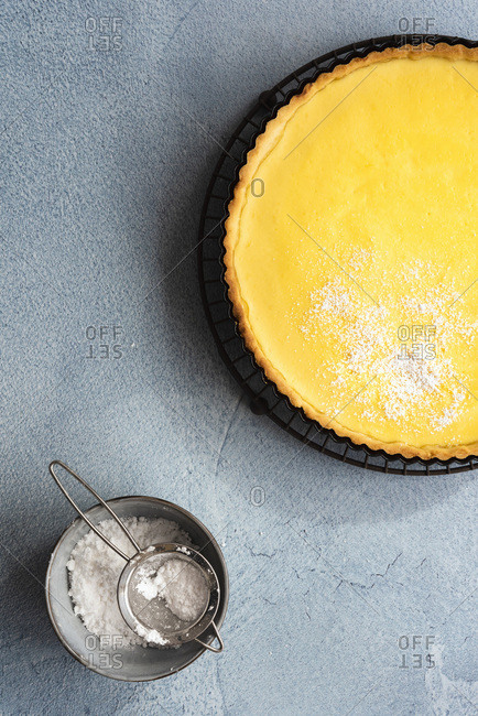 Homemade lemon tart with a bowl of icing sugar.