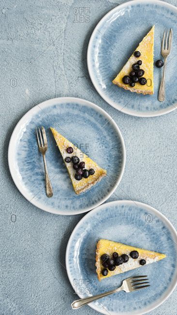 Three slices of lemon and blueberry tart on plates.