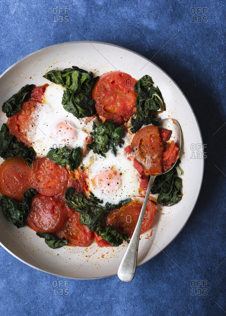 Cooked tomatoes, eggs and silver beet in a pan with a spoon.