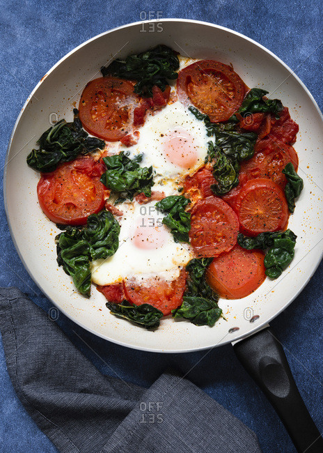 Cooked eggs, silver beet and tomatoes in a frying pan.