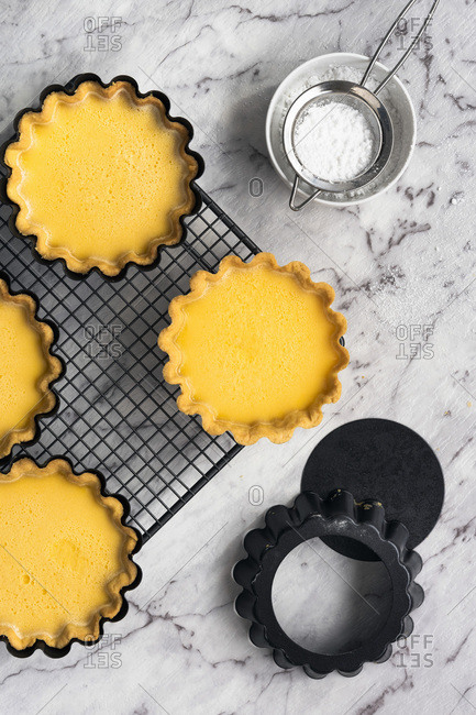 Lemon tartlets cooling on a wire cake rack.