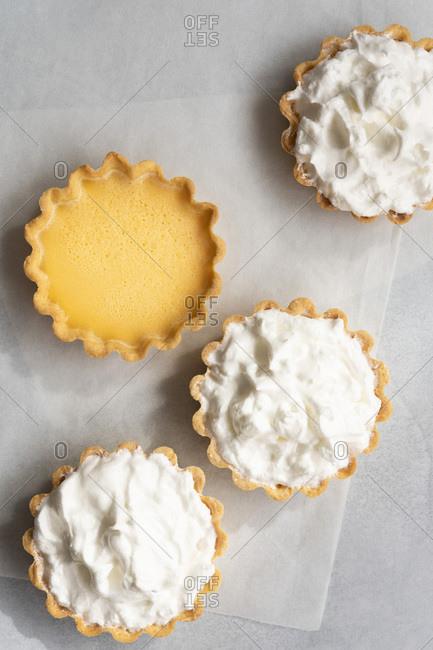 Small lemon tarts on baking paper.