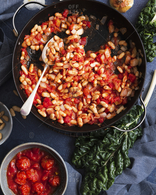 Tomatoes, cannellini beans and onions in a pan beside a bunch of silver beet and a bowl of cherry tomatoes.