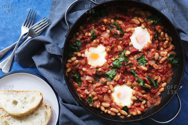 Shakshuka in a pan with crusty bread on a plate.
