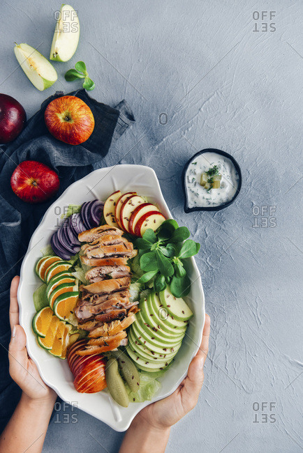 Hands placing a salad bowl with chicken salad with apples, orange slices and herbs photographed from top view.