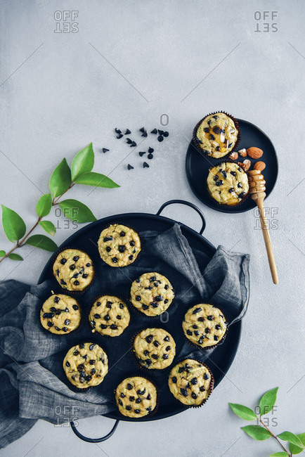 Chocolate chip zucchini muffins in a black tray and in a small black plate, a honey dipper and green leaves photographed from top view.