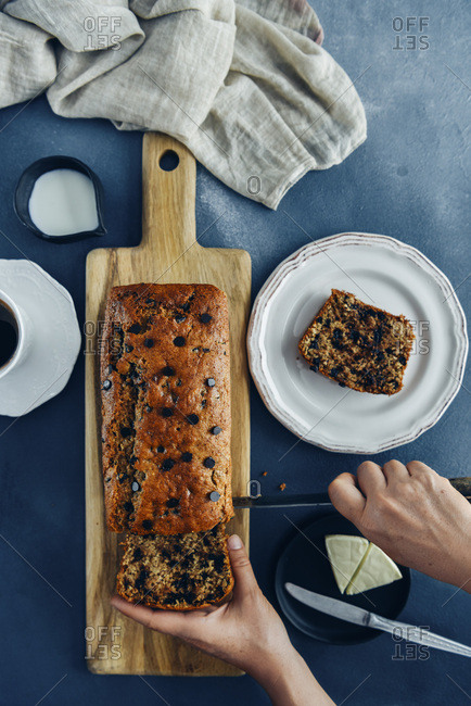 Hands slicing chocolate chip banana bread on a wooden cutting board photographed from top view.