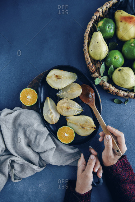 Hands holding a wooden spoon and an iron pan with caramelized pears and a wedge o orange inside. Fresh pears and oranges in a basket on the side.