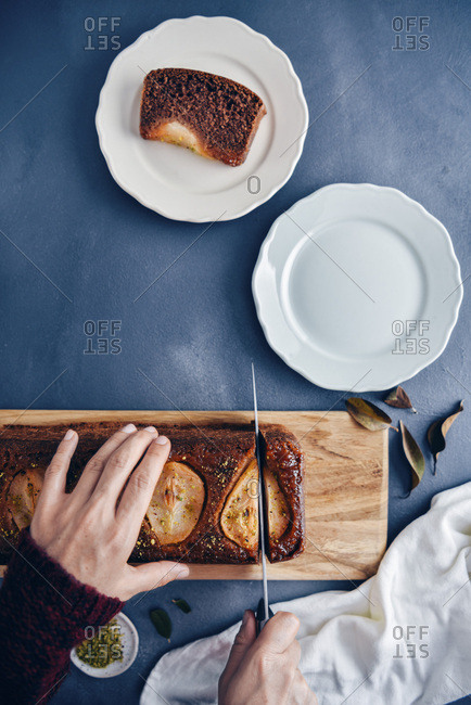 Hands slicing a pear loaf cake on a wooden board. Plates, brown leaves and pistachio in a small bowl accompany.