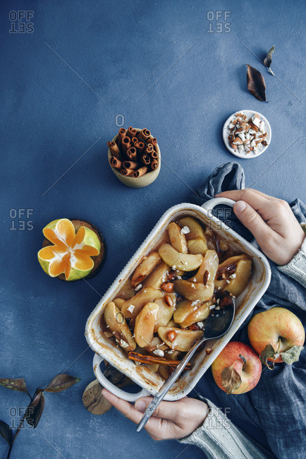 Hands holding cinnamon baked apple slices in a baking pan accompanied by apples, orange, almonds and cinnamon sticks.