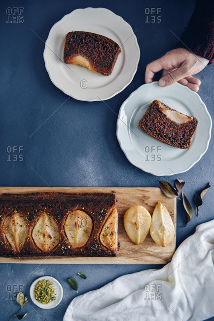Hands holding a plate with a slice of pear loaf cake on a dark backdrop. Another plate, rest of the cake on a wooden board accompany.