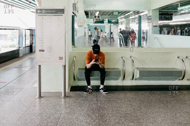 Singapore, Singapore - December 23, 2017: Young man waiting for a train
