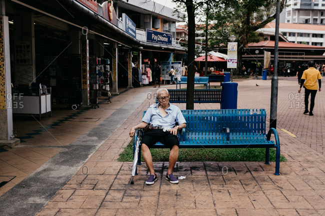 Singapore, Singapore - December 23, 2017: Elderly man sitting on a bench
