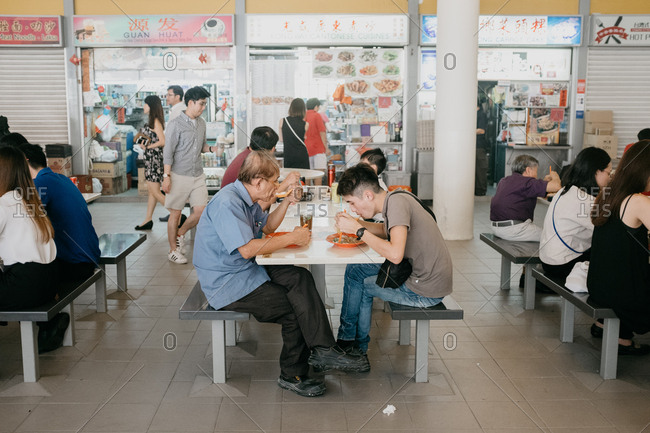 Singapore, Singapore - December 28, 2017: People eating at hawker center