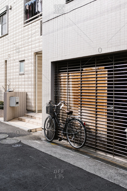 Black bicycle locked to storefront gate
