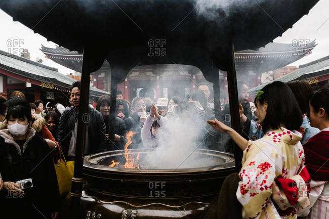 Tokyo, Japan - February 11, 2018: Woman praying at Japanese temple