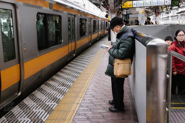 Tokyo, Japan - February 11, 2018: Man waiting for train in Tokyo