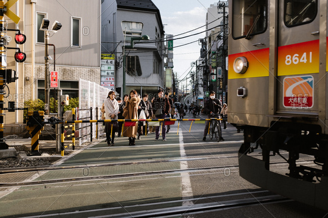 Tokyo, Japan - February 13, 2018: People waiting for train to cross road in Tokyo