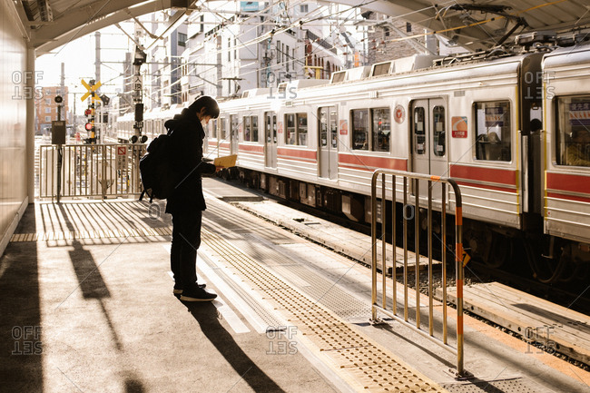 Tokyo, Japan - February 13, 2018: Man waiting for train in Tokyo
