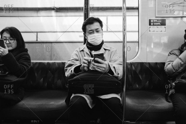 Tokyo, Japan - February 13, 2018: Man using phone in train