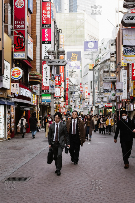 Tokyo, Japan - February 15, 2018: Business men walking through streets in Tokyo