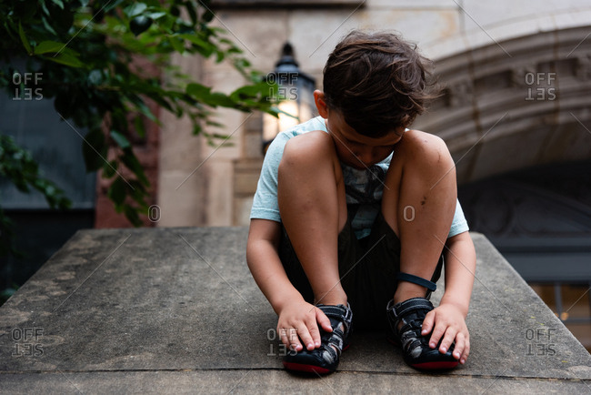 Boy sitting with his head down between his knees