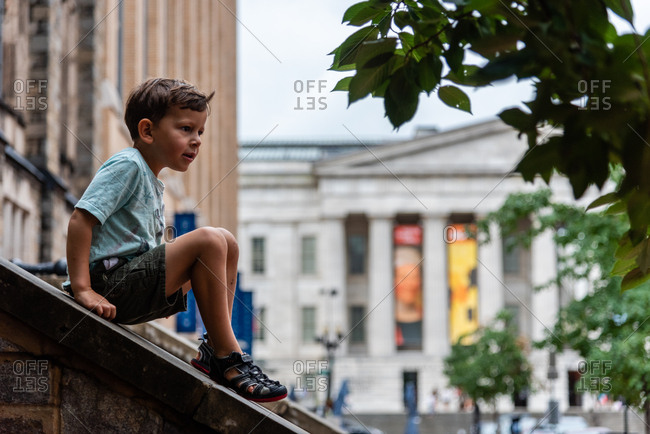 Boy sitting on the slope of an outdoor staircase looking away