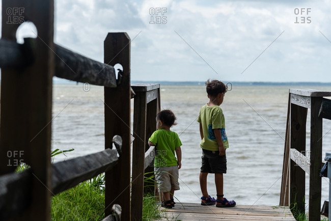 Brothers standing at end of walkway leading to the ocean
