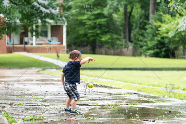 Toddler boy playing with a tennis ball outside on a rainy day