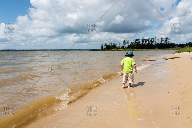 Back view of toddler boy wading in the waves on a sandy beach