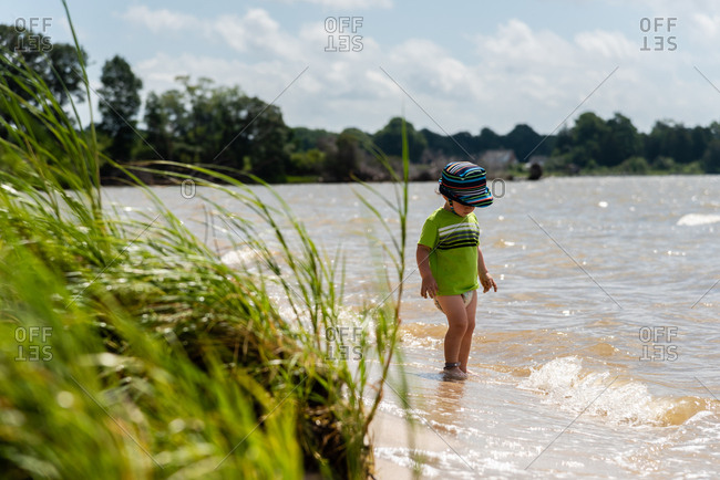 Toddler boy wearing a diaper wading in the water