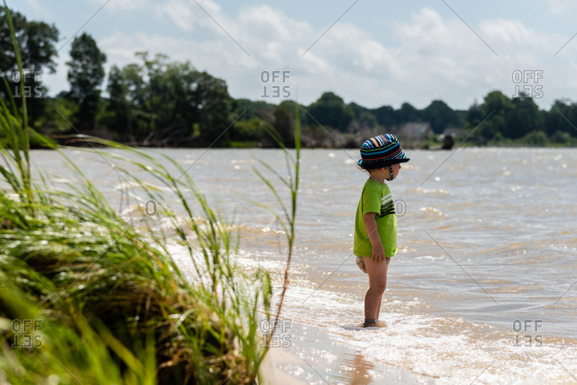Toddler boy wearing a diaper wading in the water and looking out across the bay