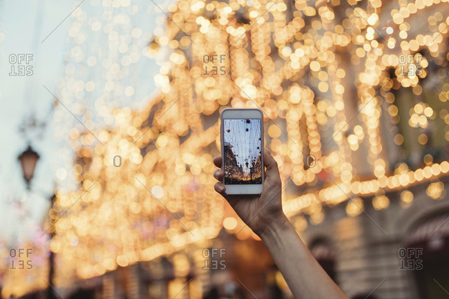 Woman taking photos of lights in Moscow with phone