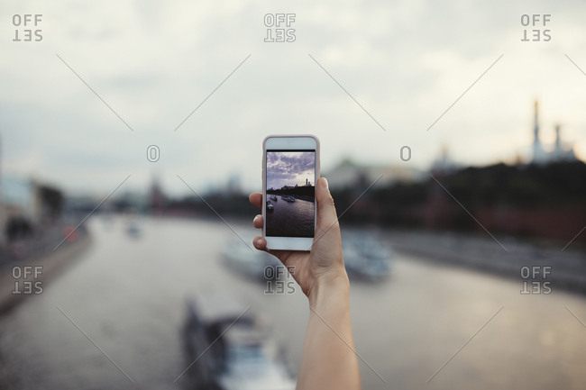 Woman taking photos of river in Moscow with phone