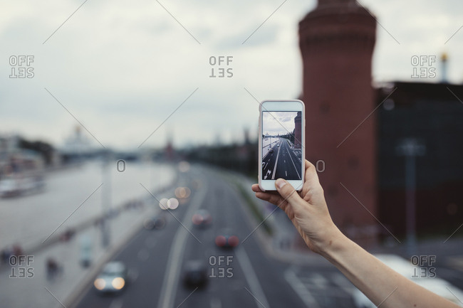 Woman taking photos of city street in Moscow with phone