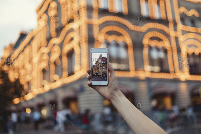 Woman taking photos of lights on a building in Moscow with phone