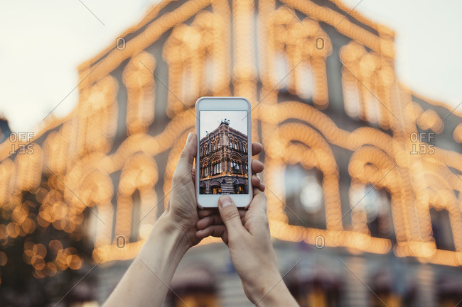 Woman taking picture of lights on a building in Moscow with phone