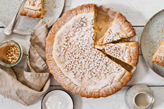 Overhead view of a custard pie topped with pine nuts