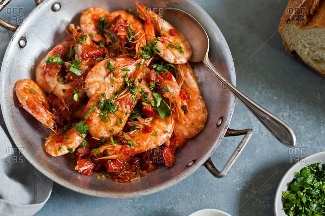 Orange shrimp and parsley in a skillet