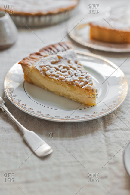 Slice of custard pie with pine nuts