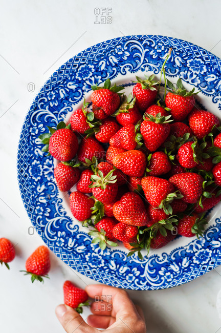 Overhead view of juicy strawberries and hand