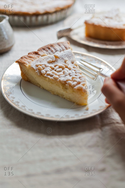 Hand eating a slice of custard pie with pine nuts